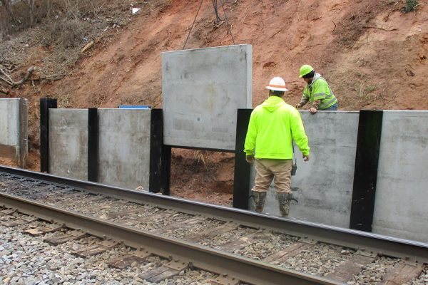 High Point Improvements - Workers place concrete panels for new retaining wall south of Wrenn Avenue